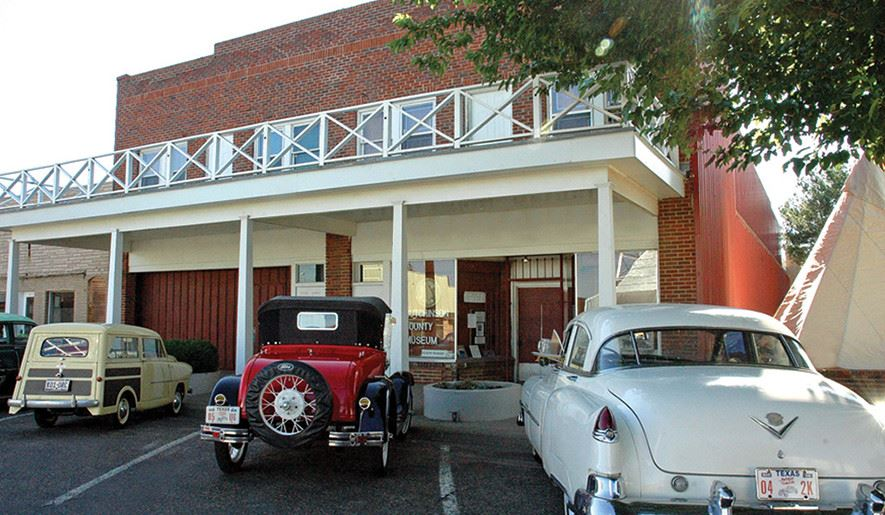 Museum Facade with old cars through the ages parked out front